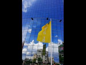 Un steag care indică scenariul corespunzător incidenței COVID-19, pus în fața Primăriei Ploiești